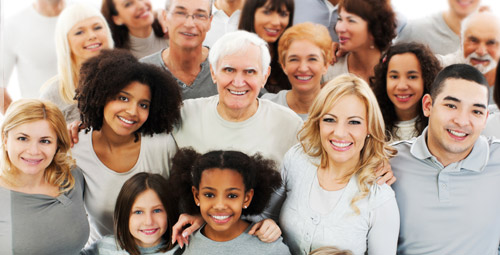 A group of people smiling who are different ages, genders and ethnicities